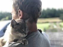 A reunião feliz do gato de olhos azuis cinzento com o proprietário após partir-se, o gato abraça gratamente o louro e os sorrisos fotografia de stock royalty free
