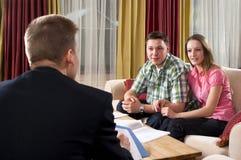 Reunião feliz dos pares com agente em casa Imagem de Stock