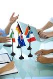 Reunião internacional com as bandeiras na tabela Fotografia de Stock Royalty Free