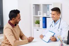 Reunião paciente feliz do doutor e do homem no hospital Foto de Stock