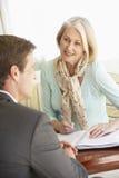 Reunião superior da mulher com conselheiro financeiro em casa Fotografia de Stock Royalty Free