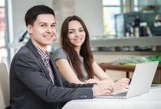¡Reunión corporativa! Empresarios jovenes que se sientan en la tabla y Imagen de archivo libre de regalías