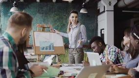 Reunión creativa del equipo del negocio en la oficina moderna La hembra del encargado que presenta datos financieros, motiva al e Fotografía de archivo libre de regalías