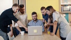 Reunión creativa del equipo del negocio que discute nuevas ideas El encargado del hombre trabaja en el ordenador almacen de video
