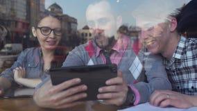 Reunión creativa en un café de dos hombres jovenes y de una muchacha metrajes