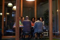 Reunión de última hora alrededor de la tabla en oficina conceptora fotografía de archivo