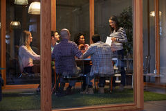 Reunión de última hora alrededor de la tabla en oficina conceptora imagen de archivo libre de regalías