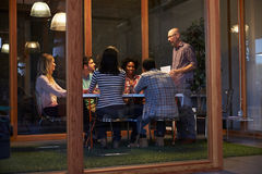 Reunión de última hora alrededor de la tabla en oficina conceptora fotografía de archivo libre de regalías