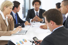 Reunión de Checking Phone During del hombre de negocios en oficina Imagenes de archivo
