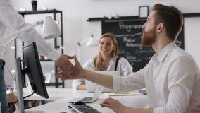 Reunión de funcionamiento del hombre de negocios con el apretón de manos para el equipo acertado en oficina almacen de video