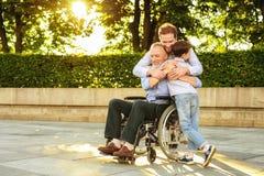 reunión de la familia Un hombre y un muchacho vinieron ver a su abuelo que se sienta en un parque en una silla de ruedas foto de archivo