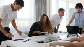 Reunión de la gente de la oficina en la tabla para discutir el desarrollo de negocios de las ideas en la sala de reunión almacen de metraje de vídeo