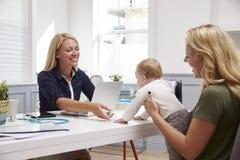 Reunión de la madre y del bebé con el doctor de sexo femenino In Office Fotografía de archivo libre de regalías