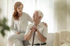 Reunión de la nieta sonriente con el abuelo feliz con wal fotos de archivo