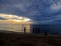 Reunión de la silueta sobre la playa en puesta del sol Imagen de archivo libre de regalías