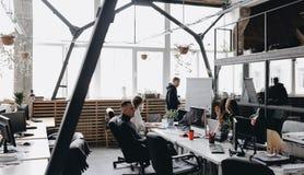 Reuni?n de los colegas Un equipo que se sienta en las tablas con los ordenadores y los ordenadores port?tiles y que escucha el co fotografía de archivo libre de regalías