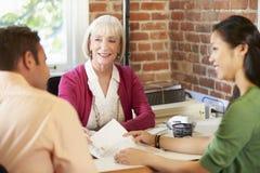 Reunión de los pares con el consejero financiero en oficina Fotos de archivo