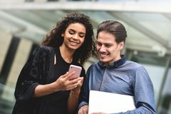 Reunión de negocios Hombre y mujer que discuten el trabajo y que miran la pantalla del smartphone Trabajo junto en el aire abiert fotografía de archivo