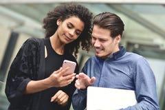 Reunión de negocios Hombre y mujer que discuten el trabajo y que miran la pantalla del smartphone Trabajo junto en el aire abiert imagenes de archivo