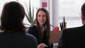 Reunión de negocios - la empresaria joven escucha su compañero de trabajo y sonríe