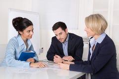 Reunión de negocios Tres personas que se sientan en la tabla en una oficina imagen de archivo