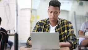 Reunión de reflexión africana joven de pensamiento del hombre y trabajo en el ordenador portátil metrajes