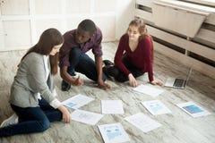 Reunión de reflexión creativa multirracial del equipo en el piso de la oficina Imagenes de archivo