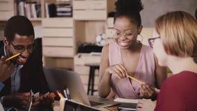 Reunión de reflexión femenina afroamericana alegre del encargado con los colegas multiétnicos felices en oficina sana del desván  metrajes