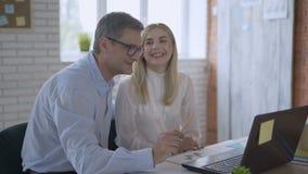 Reunión de reflexión joven de la mujer del líder de equipo con el colega del hombre de negocios que usa el ordenador portátil que metrajes
