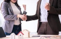 Reunión del agente y del cliente de seguro que sacuden la mano después de firmar el contrato para la compra de los bienes raice imagenes de archivo