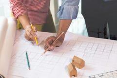 Reunión del arquitecto o del ingeniero, funcionamiento con los modelos en oficina fotos de archivo libres de regalías
