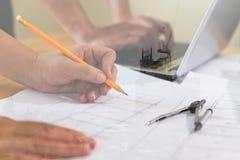 Reunión del arquitecto o del ingeniero, funcionamiento con los modelos y lapto fotografía de archivo libre de regalías