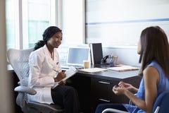 Reunión del doctor Wearing White Coat con el paciente femenino Imágenes de archivo libres de regalías