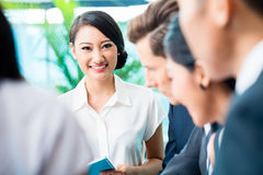 Reunión del equipo del negocio de ejecutivos asiáticos y caucásicos imagenes de archivo