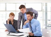 Reunión del equipo del negocio usando el ordenador portátil en la oficina fotos de archivo