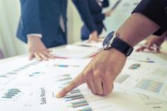 Reunión del equipo directivo que discute la carta de los datos en la tabla imagen de archivo libre de regalías