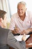 Reunión del hombre mayor con el consejero financiero en casa Fotografía de archivo libre de regalías