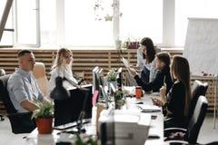 Reunión del personal de un equipo acertado joven en la oficina moderna ligera equipada del mobiliario de oficinas moderno fotografía de archivo libre de regalías