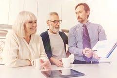 Reunión envejecida positivo de los pares con el agente inmobiliario imagen de archivo libre de regalías