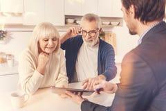 Reunión envejecida positivo de los pares con un agente inmobiliario foto de archivo libre de regalías