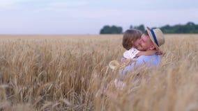 Reunión feliz, pequeña muchacha linda que abraza al hombre feliz en campo de trigo durante la estación de la cosecha contra el ci almacen de video