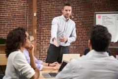 Reunión joven de la oficina de Standing And Leading del hombre de negocios alrededor de la tabla fotografía de archivo