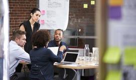Reunión joven de la oficina de Standing And Leading de la empresaria alrededor de la tabla imagen de archivo libre de regalías