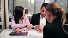 Reunión joven de los pares con el consejero financiero almacen de metraje de vídeo