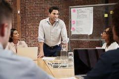 Reunión madura de la oficina de Standing And Leading del hombre de negocios alrededor de la tabla fotos de archivo