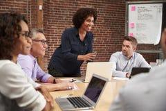 Reunión madura de la oficina de Standing And Leading de la empresaria alrededor de la tabla imágenes de archivo libres de regalías