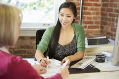 Reunión mayor de la mujer con el consejero financiero en oficina imagen de archivo libre de regalías