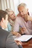 Reunión mayor de los pares con el consejero financiero en casa que parece preocupado foto de archivo