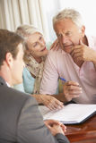 Reunión mayor de los pares con el consejero financiero en casa que parece preocupado imágenes de archivo libres de regalías