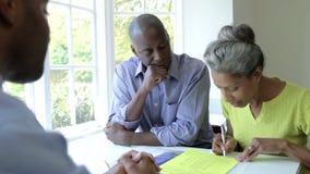 Reunión negra madura de los pares con el consejero financiero en casa almacen de video